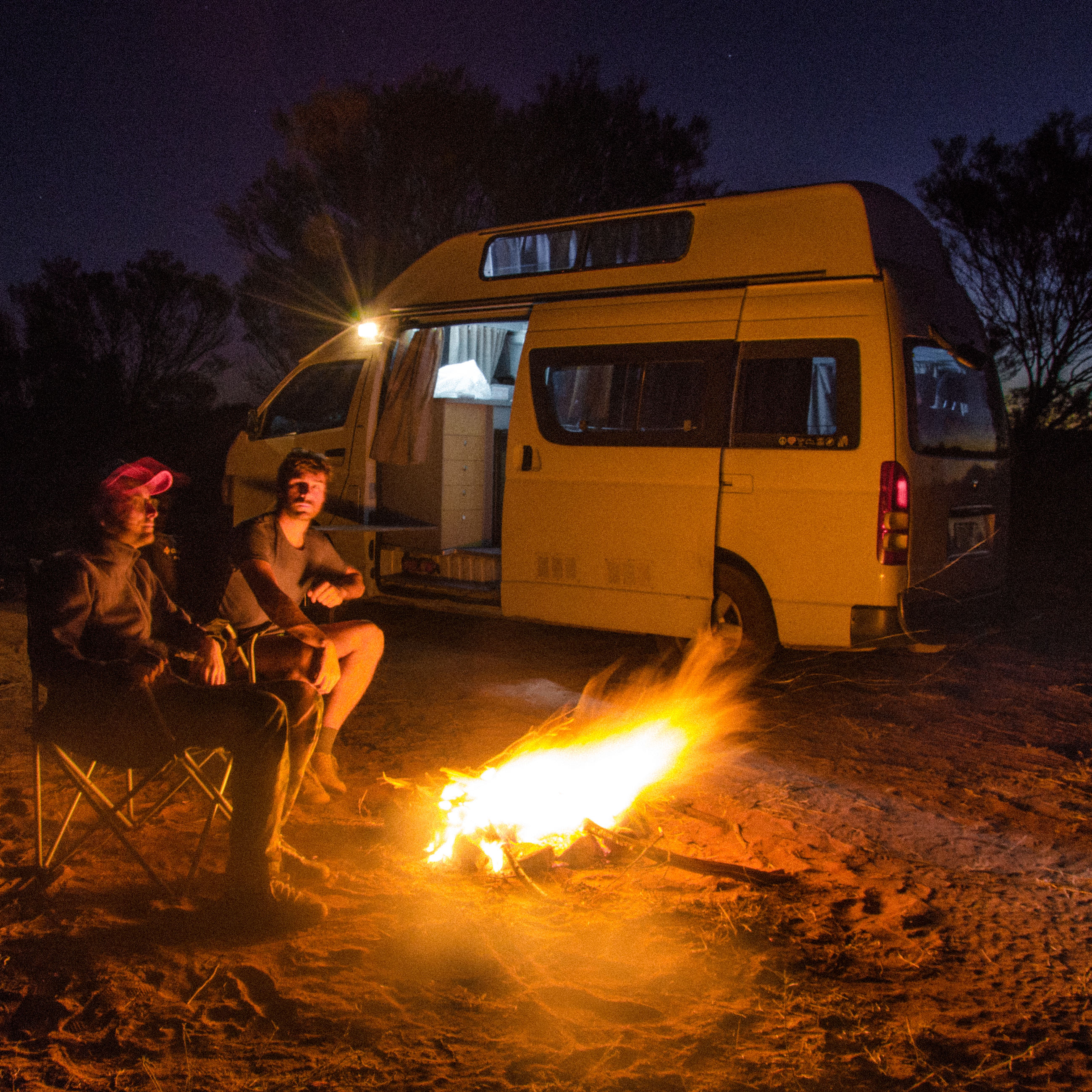 flame, heat - temperature, mode of transportation, fire, burning, night, nature, fire - natural phenomenon, two people, men, real people, transportation, land vehicle, people, illuminated, adult, camping, bonfire, women, young adult, campfire, outdoors