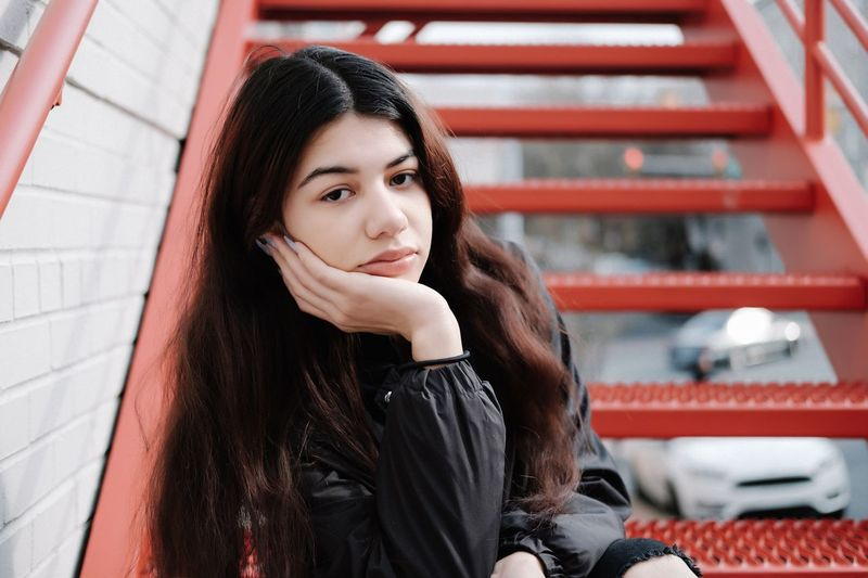 Portrait of beautiful young woman sitting on steps
