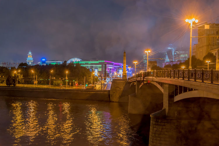 Bridge over moskva river in illuminated city at night