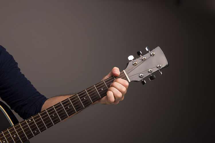 Cropped image of musician playing guitar against gray background
