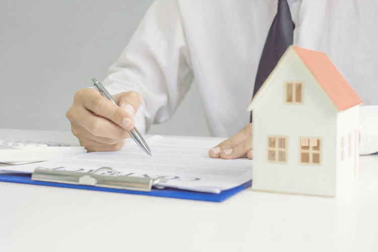 Midsection of real estate agent with contract paper working on table
