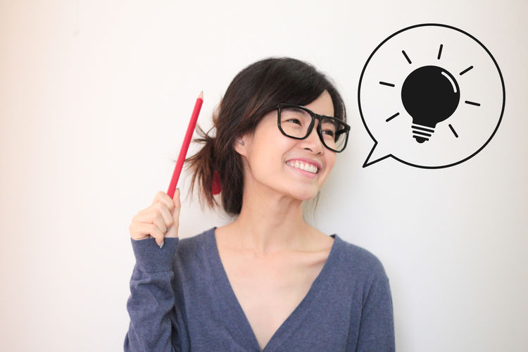 Asian girl wearing glasses and smile in class with good idea icon Asian  Glasses Happiness Happy Intelligent Nerd Nerdy Smart Student Thinking Adult Book Classroom Girl Headshot Idea Indoors  Intelligence One Person Pencil People Portrait Smile Teacher White Background
