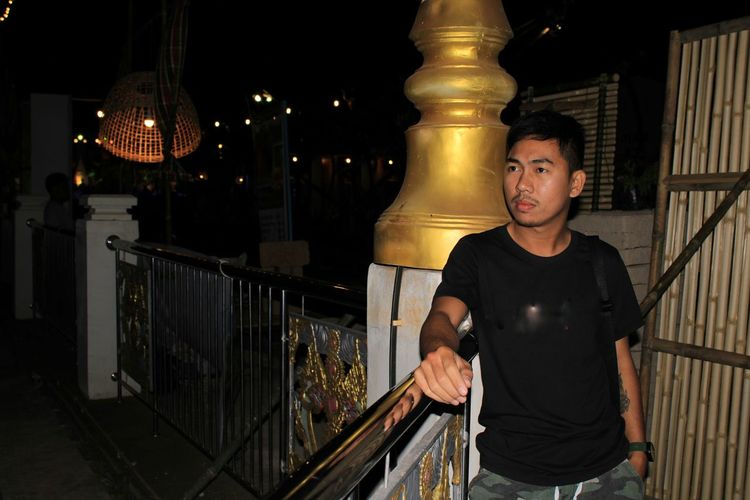 Portrait of young man standing against railing at night
