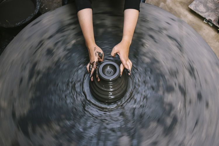 Hands of a nepalese pottery. selection focus with motion blur