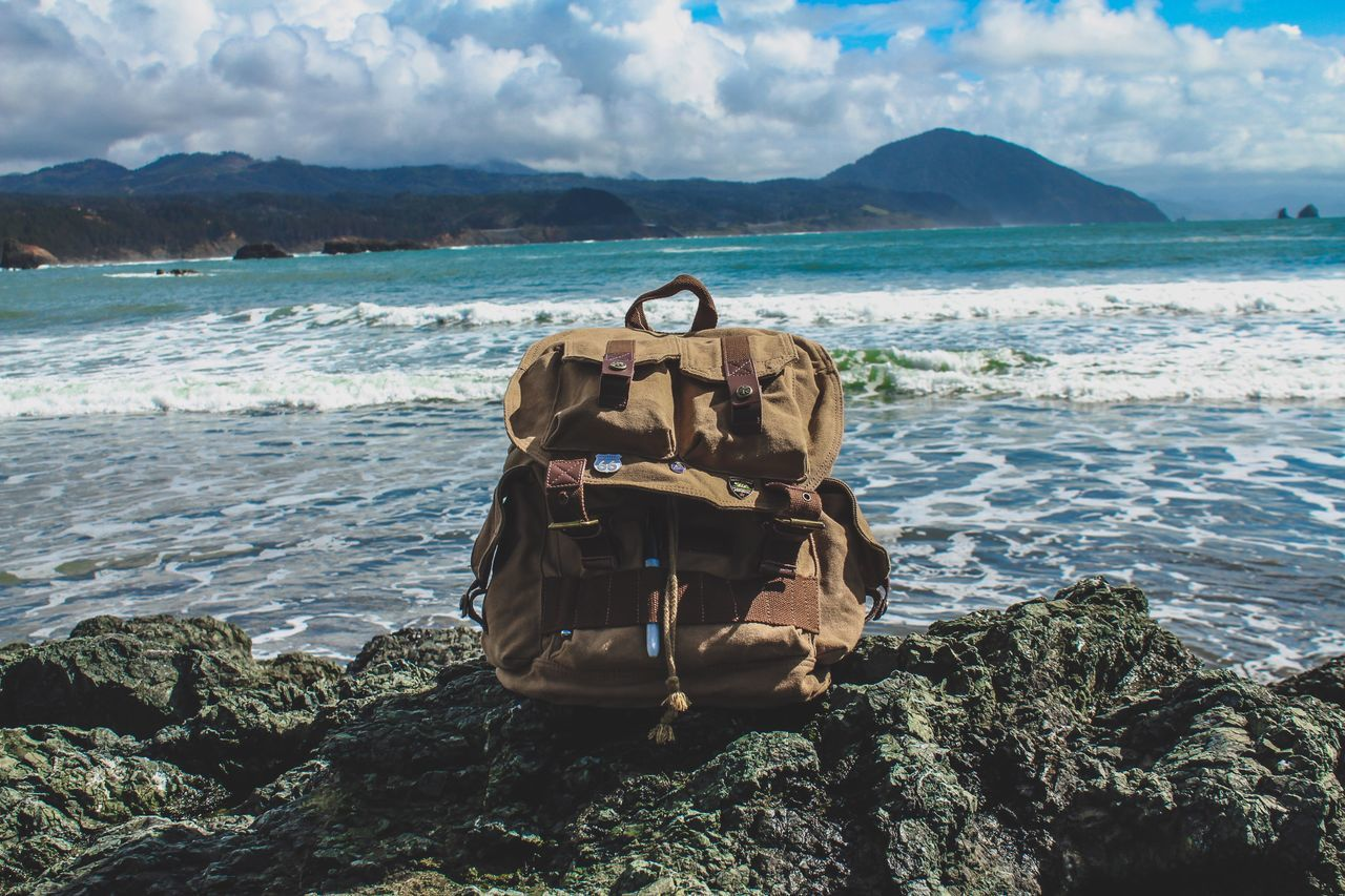 Backpack On Rock Against Sea