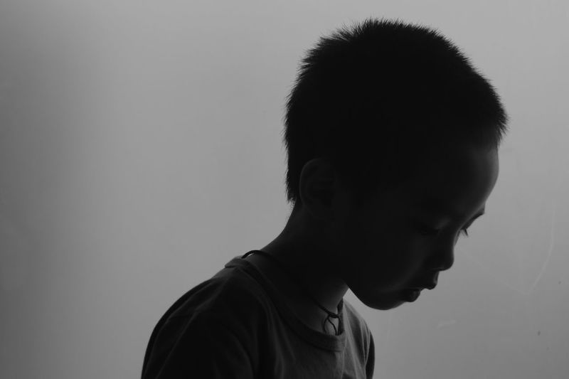 Side view of boy against gray background