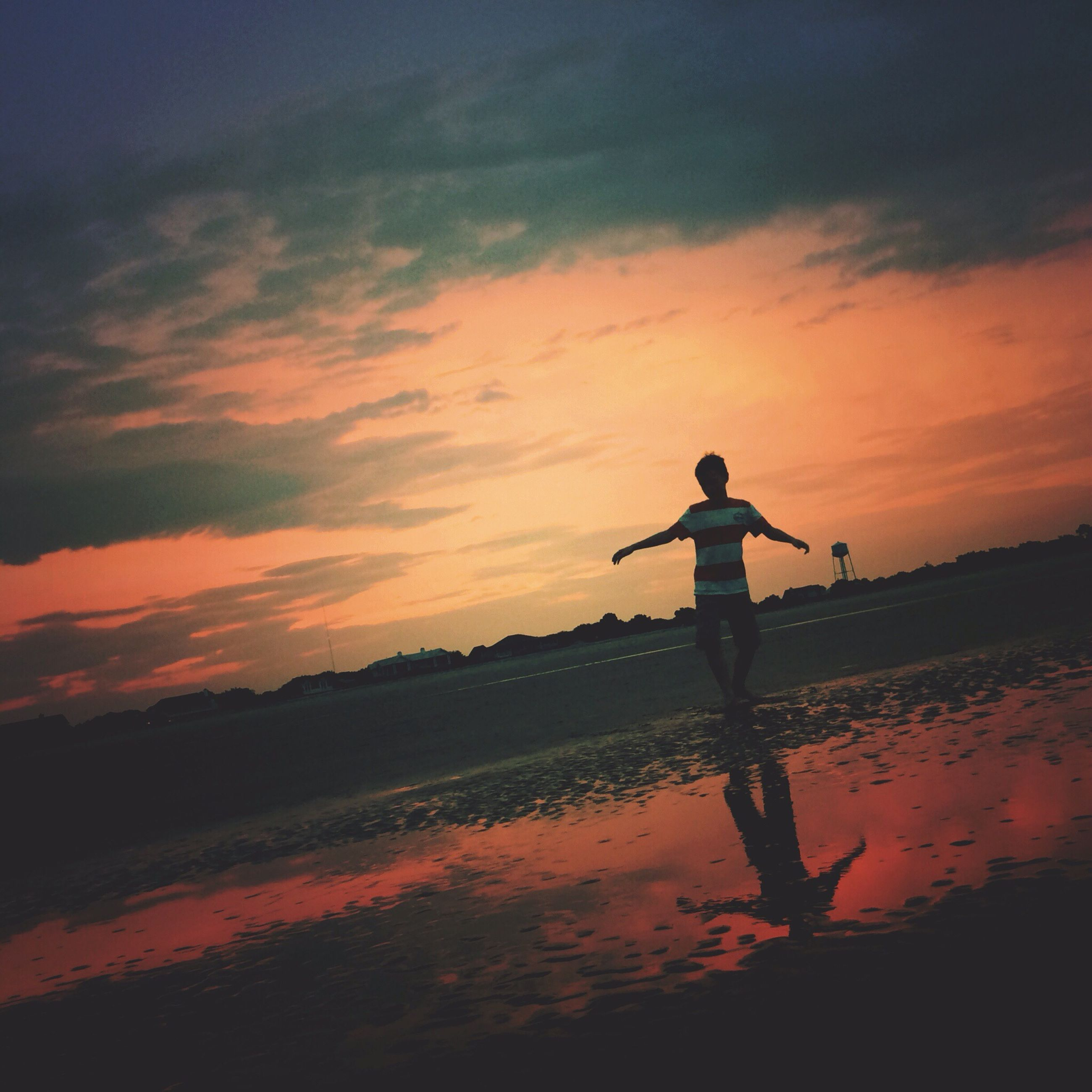sunset, water, silhouette, sky, leisure activity, full length, lifestyles, orange color, sea, standing, scenics, tranquil scene, beauty in nature, beach, tranquility, shore, nature, cloud - sky