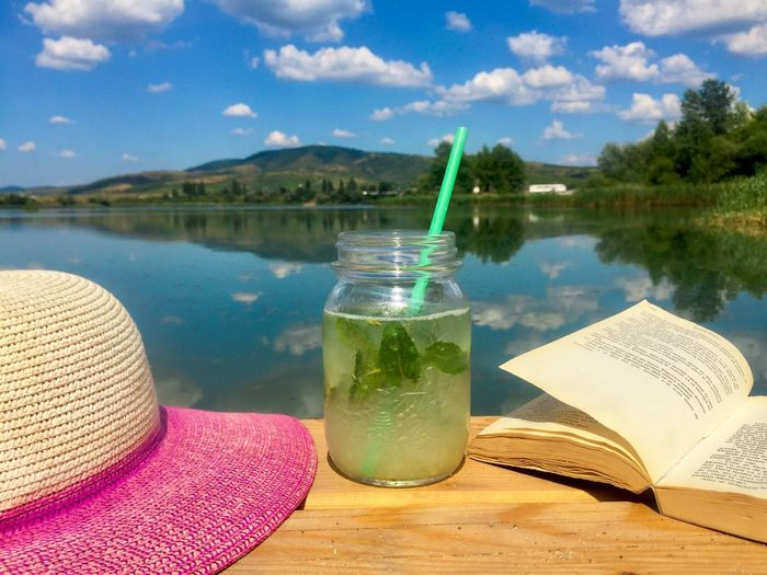 Drinking glass on table by lake