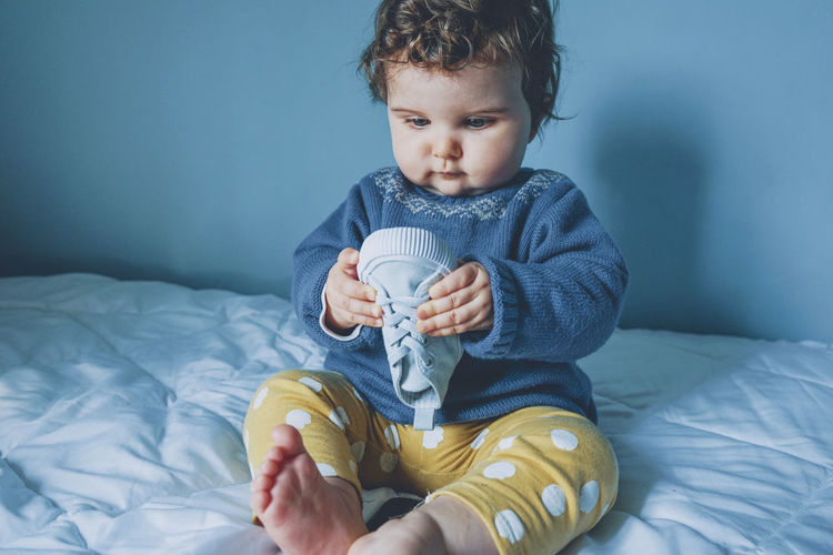Cute baby boy sitting on bed at home