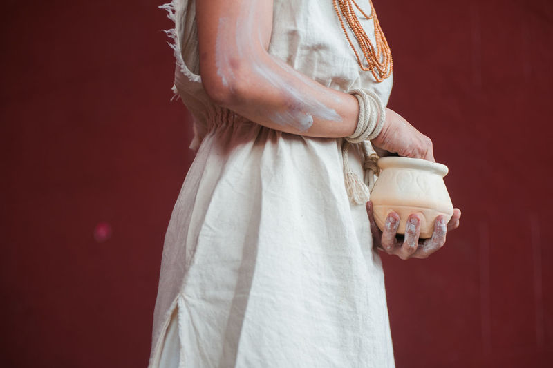 Midsection of woman with pot standing against wall
