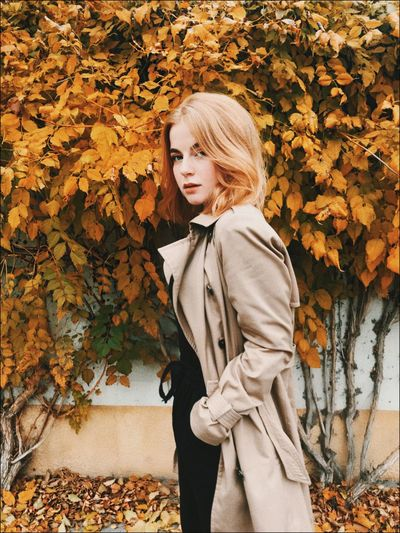 Young woman standing by leaves during autumn