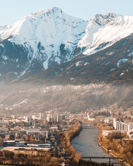 Aerial view of city by snowcapped mountains