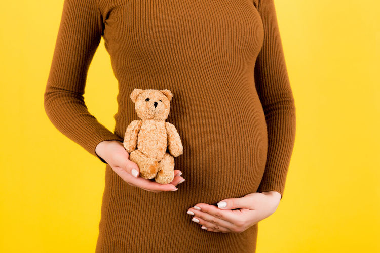 Midsection of woman with stuffed toy against yellow background