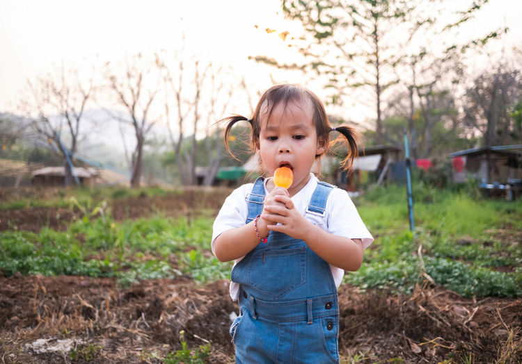 Girl eating flavored ice while standing on land