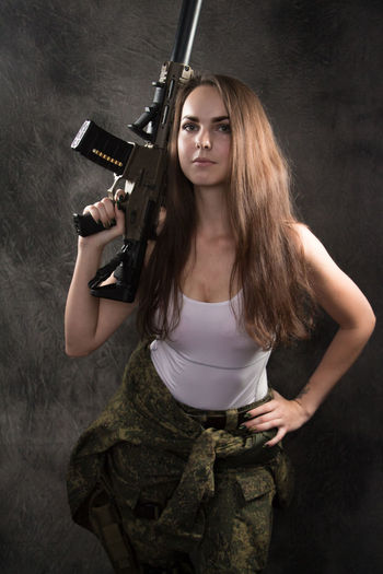 Aggression  Beautiful Woman Beauty Clothing Fashion Gun Hair Hairstyle Handgun Holding Indoors  Long Hair Looking At Camera One Person Portrait Standing Studio Shot Teenager Three Quarter Length Uniform Weapon Young Adult