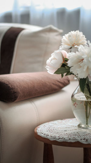 Midsection of person holding bouquet at home