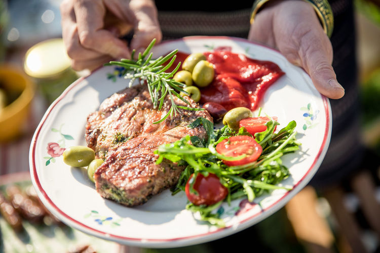 Food And Drink Arugula Barbecue Close-up Focus On Foreground Food Food And Drink Freshness Garnish Grill Hand Healthy Eating Herb Holding Human Body Part Human Hand Meat One Person Plate Ready-to-eat Real People Table Tomato Vegetable