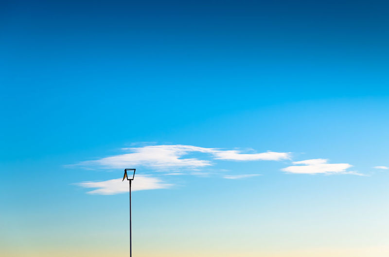 Low angle view of lamp post against blue sky