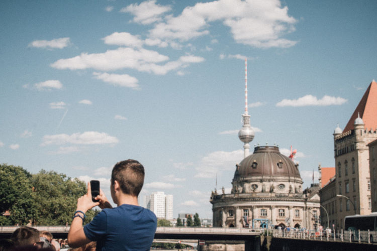 Rear view of man photographing in city with fernsehturm in background
