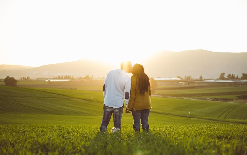 Rear view of couple kissing while standing on field against sky during sunset