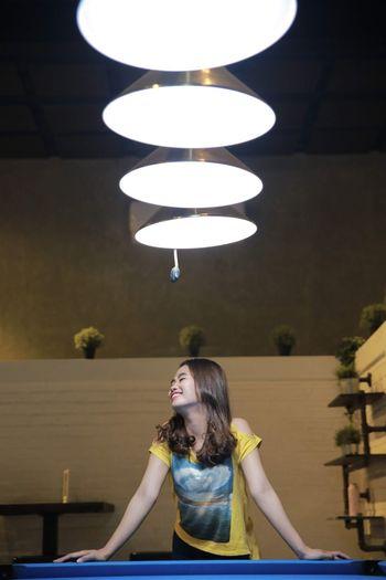 Smiling woman standing under illuminated pendant lights