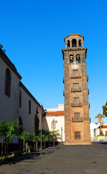Bell tower of church in city against clear blue sky on sunny day