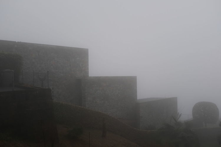 Buildings against sky during foggy weather