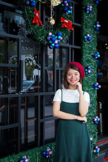 Portrait of smiling young woman standing against window during christmas