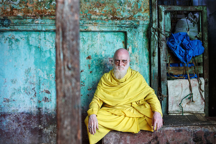 A man in yellow at the fish market in Varanasi, India. ASIA India Varanasi One Person Portrait Travel
