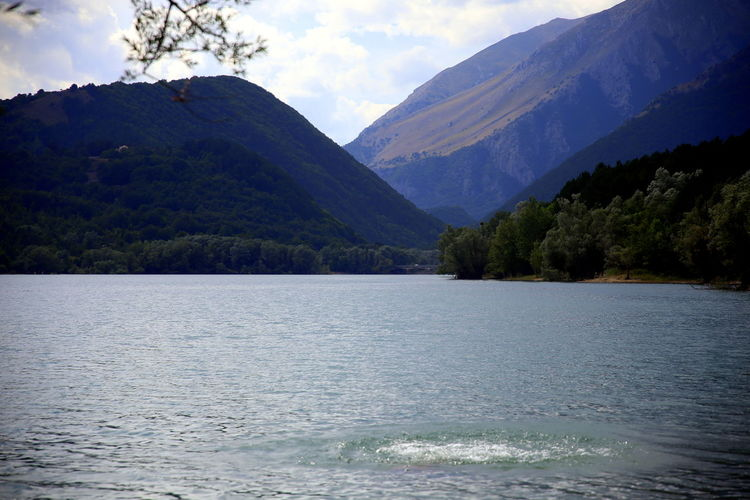 A dip in the lake among the green tree-lined mountains, abruzzo region, italy