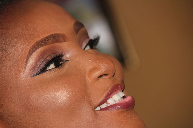 Close-up of woman wearing make-up at home
