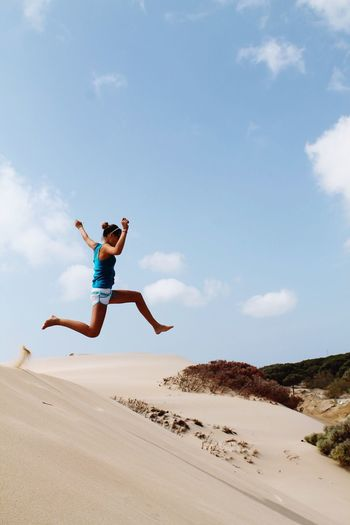 Low angle full length of woman jumping over sand against sky during sunny day