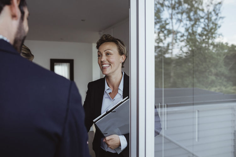 Smiling young woman standing against window