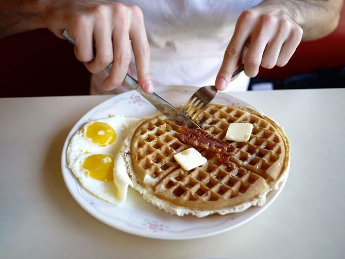 Midsection of man eating waffle at table