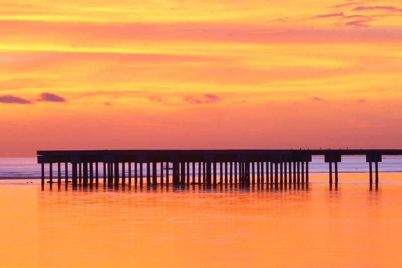 Silhouette Pier On Sea Against Orange Sky