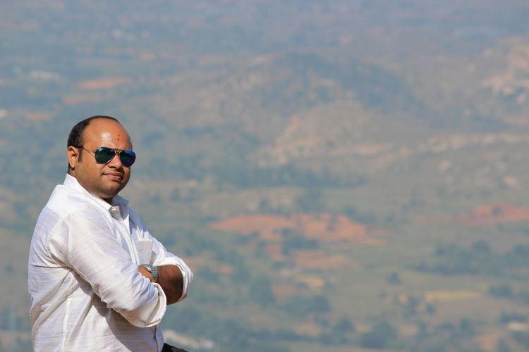 Portrait of man wearing sunglasses against landscape