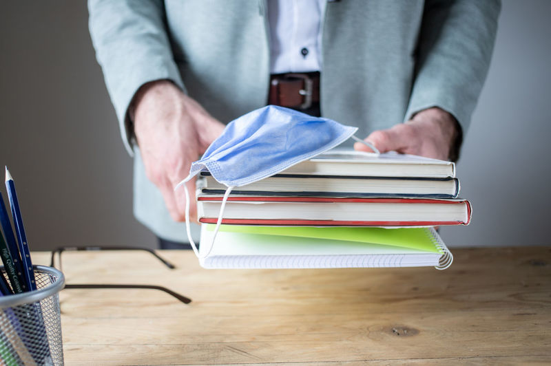 Midsection of man working on book