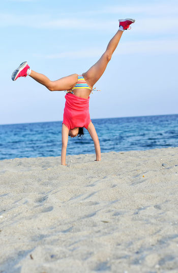 Woman doing a cartwheel on beach against sky