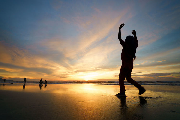 Low Angle View Of Silhouette Man With Arms Raised Walking At Beach During Sunset