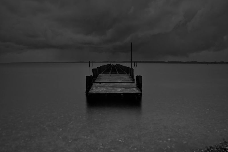 Boat on sea against storm clouds