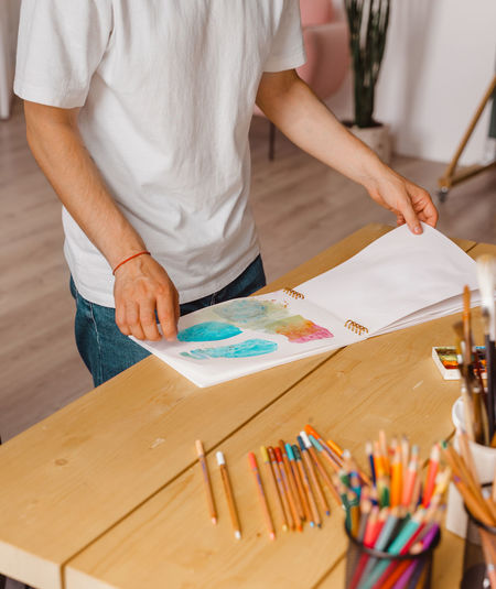 Attractive young creative man.sketchbook.wooden table. concept diy. real art maker in action