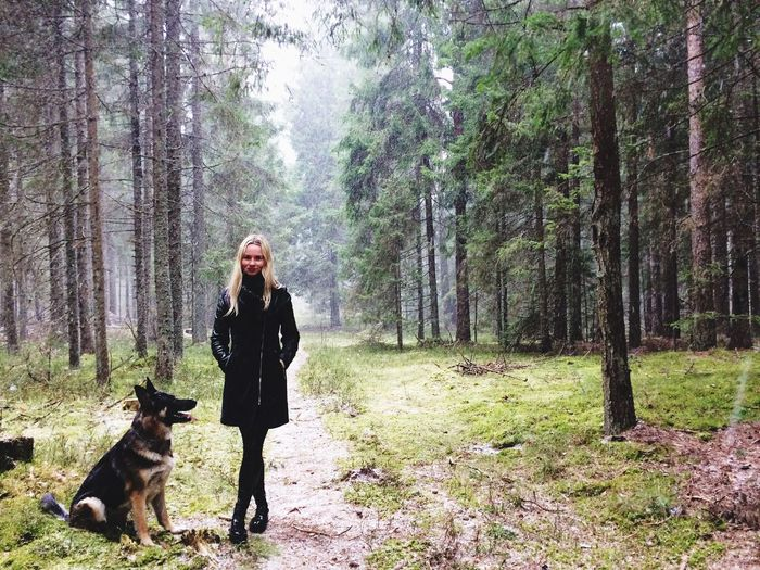 Portrait Of Woman With Dog Standing On Field At Forest