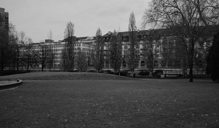 Empty park by buildings against sky
