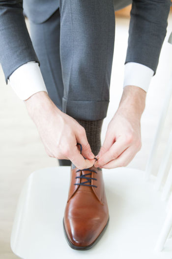 Low Section Of Bridegroom Tying Shoelace On Chair