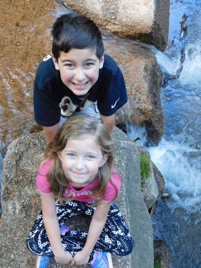 Kids by the Waterfall Children Kids Waterfall Waterfalls Brother & Sister Siblings Childhood Child Girls Looking At Camera Females Portrait Women Smiling Happiness Real People Togetherness Leisure Activity High Angle View Front View Emotion Offspring Family Bonding Cute