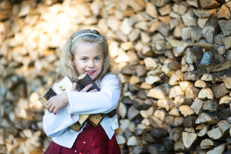 little beautiful girl with firewood Backgrounds Blond Hair Child Childhood Children Only Cute Day Firewood Girl Portrait Girls Happiness Little Girl Long Hair Looking At Camera Natural Beauty Work One Girl Only One Person Working People Portrait Smiling Stack Standing Woodpile Business Stories