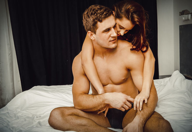 Young woman embracing man on bed at home