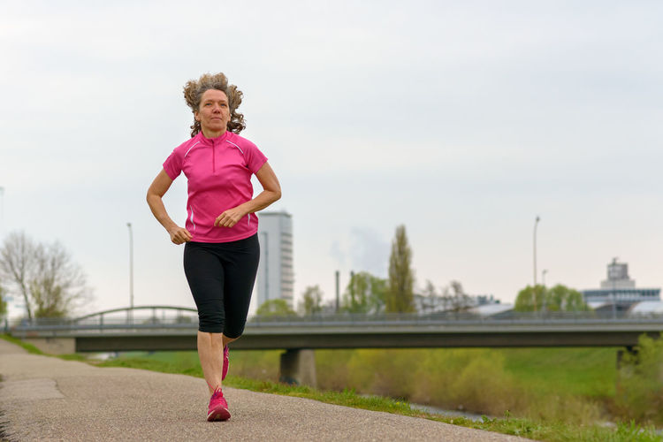 One Person Exercising Lifestyles Sport Real People Healthy Lifestyle Full Length Sports Clothing Running Leisure Activity Day Clothing Vitality Pink Color Sky Determination Focus On Foreground Front View Effort Physical Activity Body Conscious Outdoors