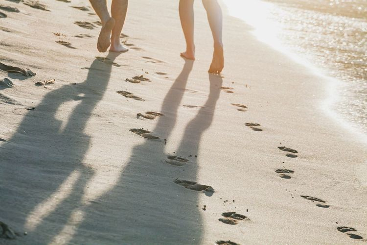 Low section of people walking at beach