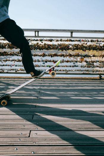 Low section of man skate boarding in paris city on a bridge against sky